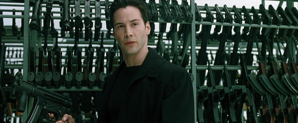 Keanu Reeves as Neo in the matrix: standing next to a large inventory of weapons for the final action scene in the movie.