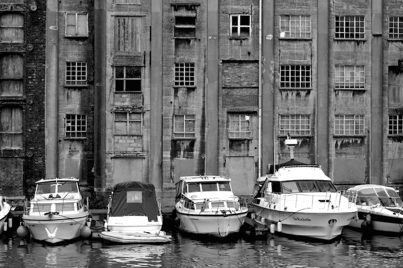 Black & white photo of ruined dockside buildings and boats