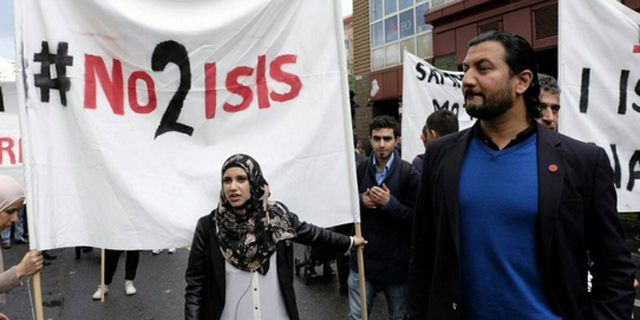 "A group of protestors that are anti-ISIS that are holding a sign that says: ""No 2 ISIS"""