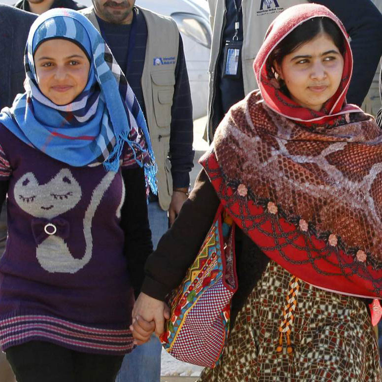Malala holding hands with a refugee