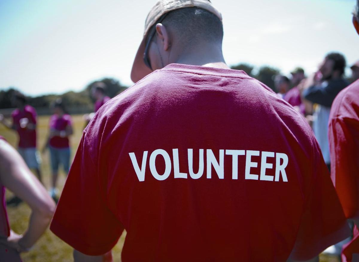 A man in a red shirt which says 'Volunteer'