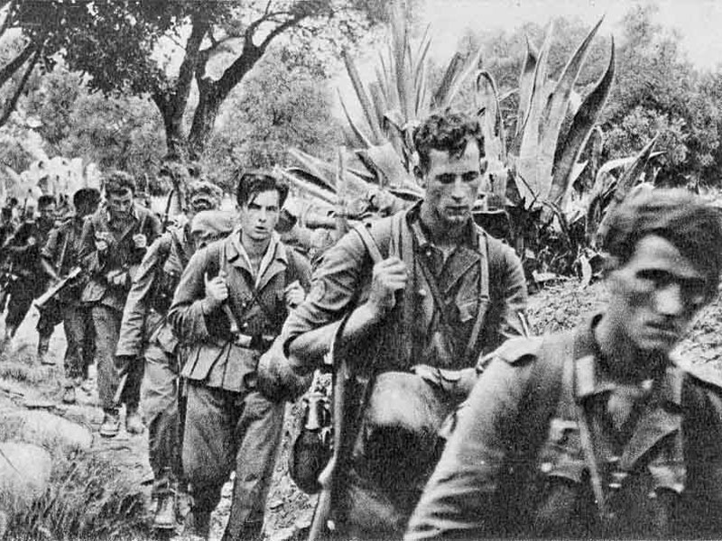 Young, tired soldiers carry their kit on a long march