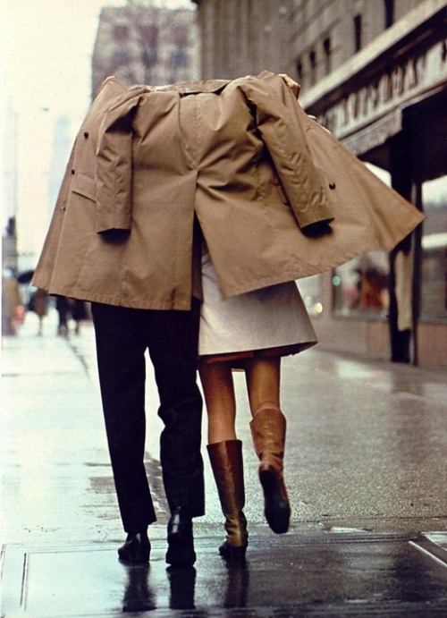 An image of a couple sharing a coat to cover each other from the rain