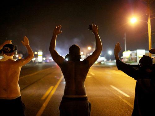 Men in Ferguson raise their hands against the police