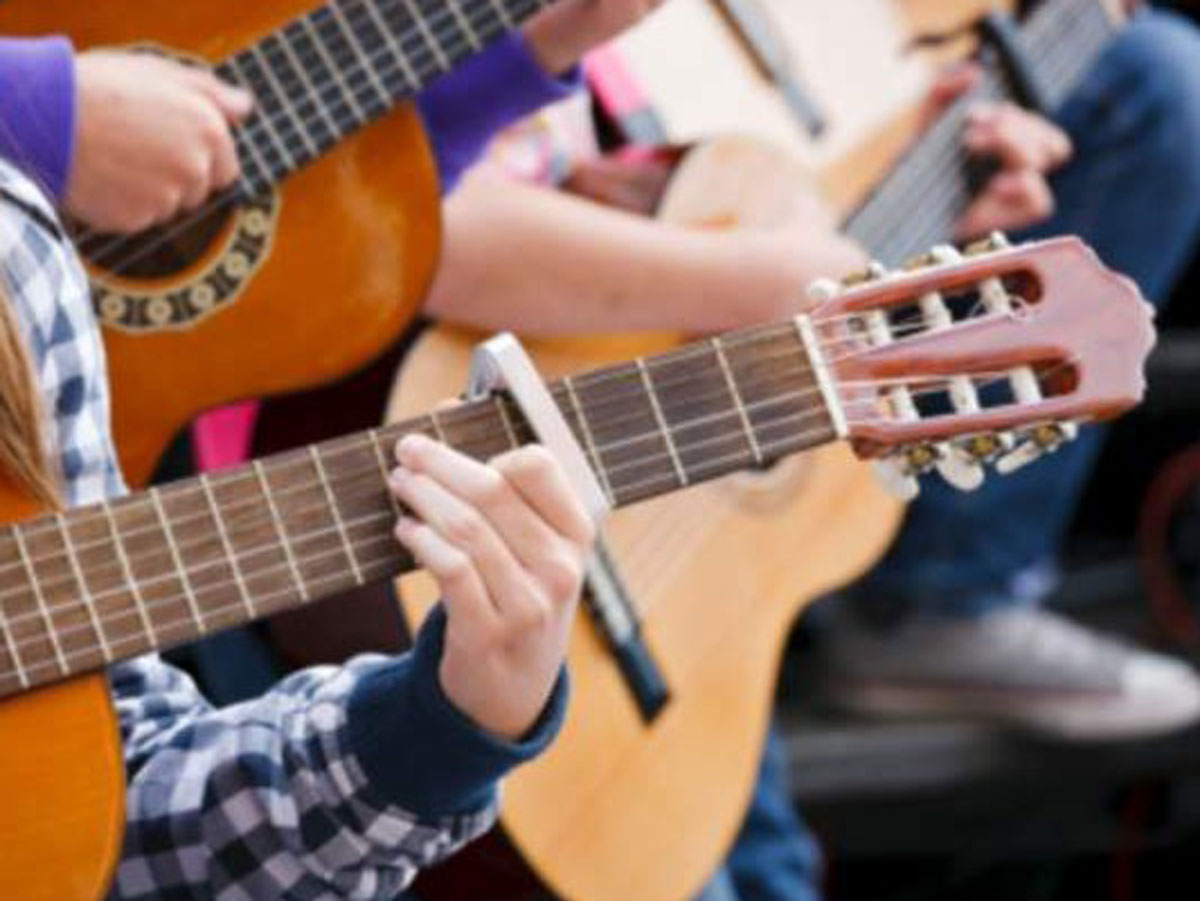 Young people play acoustic guitars