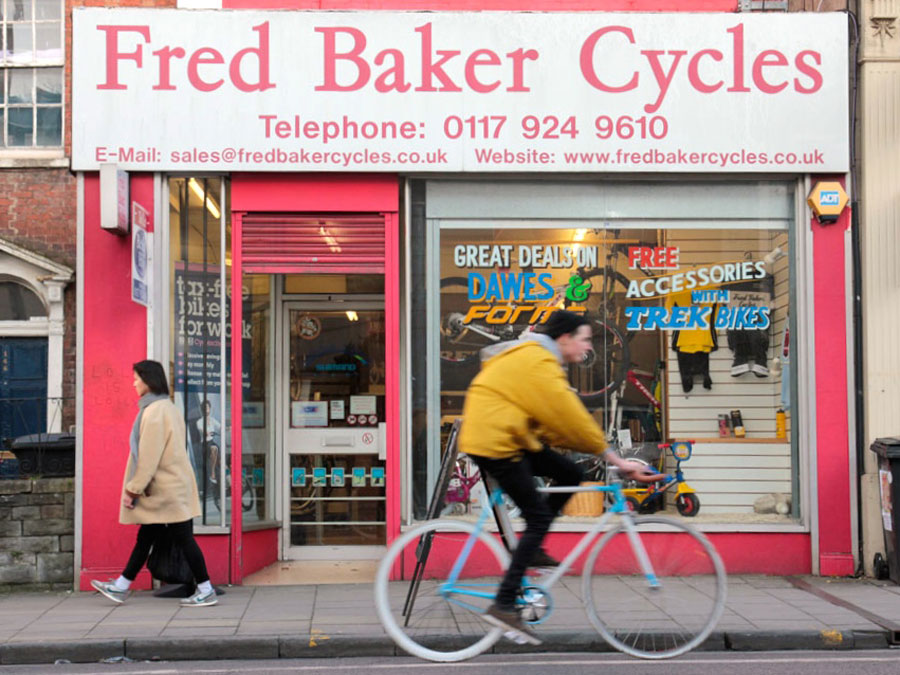 A cyclist going past Fred Baker Cycles