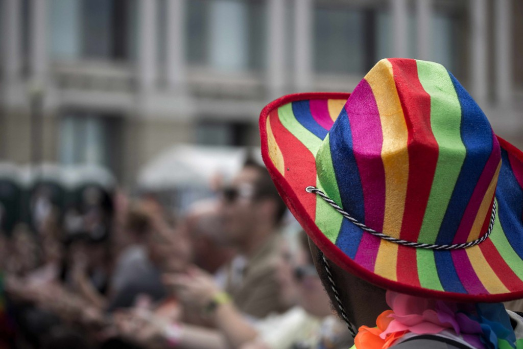 Guy with a rainbow cowboy hat glances into the crowd.